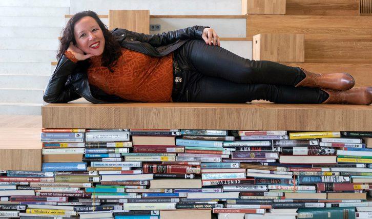 Relaxed liggend op een stapel boeken.